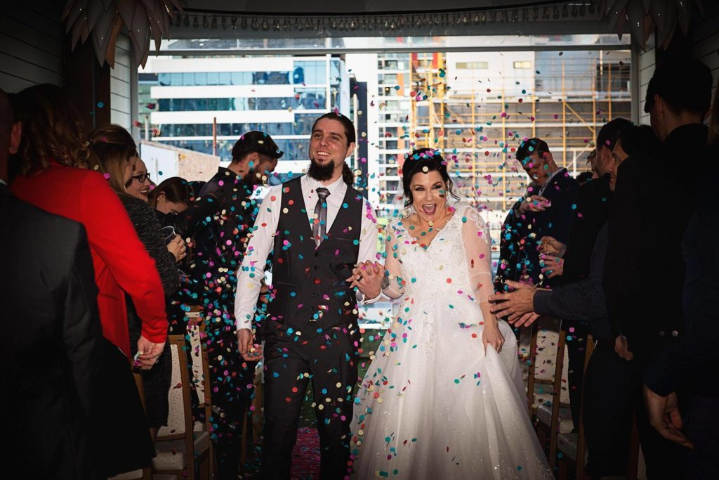 Bride and groom walking down the aisle with confetti in Brisbane
